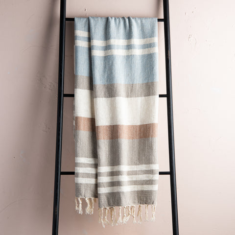 light blue, cream, taupe, and rust striped throw blanket with beige tassel fringe