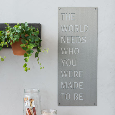 "metal quote sign that reads ""the world needs who you were made to be"""