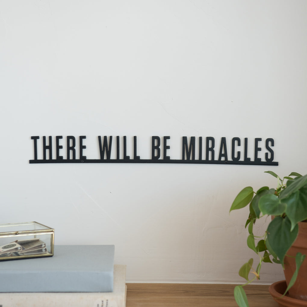 "black metal wall expression that reads ""there will be miracles"""