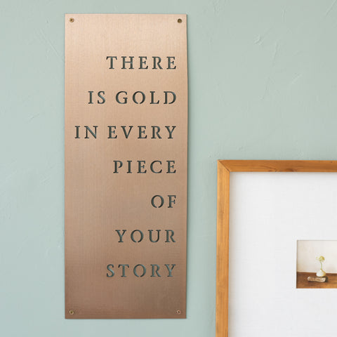 "gold finished metal quote sign with laser-cut quote reading ""There is gold in every piece of your story"""