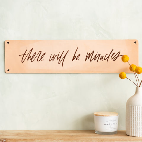 "light leather sign with phrase ""there will be miracles"" in modern script"
