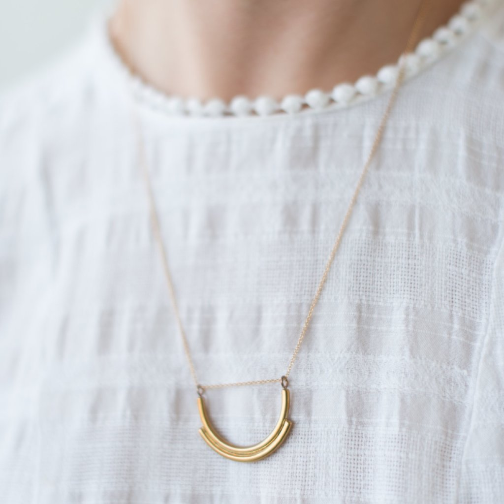 gold necklace with half-moon pendant