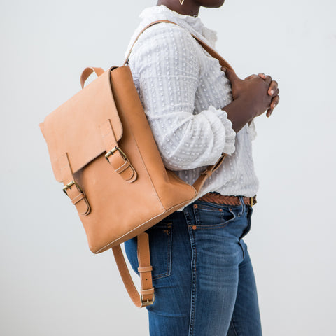 light brown leather backpack with buckle closure