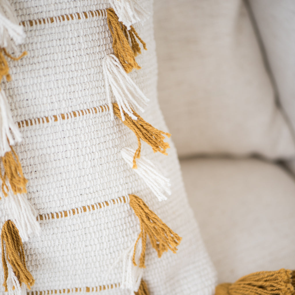 white pillow with mustard colored tassel detail