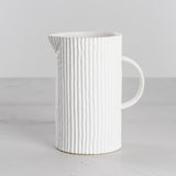 white ceramic pleated pitcher with spout and handle