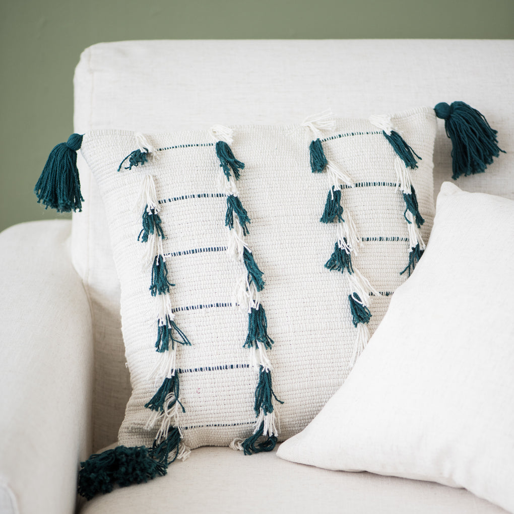 white pillow with teal tassel detail
