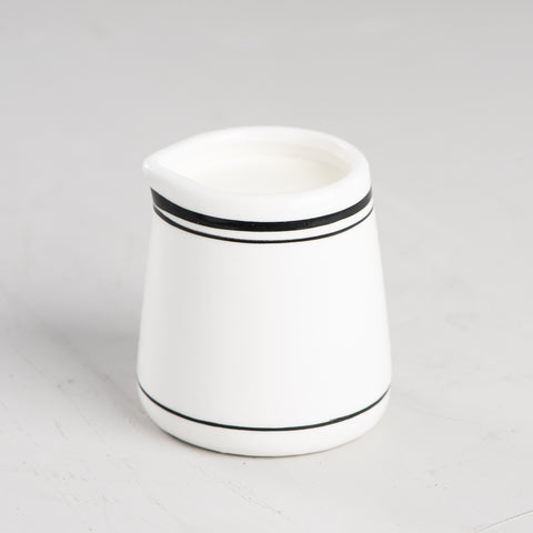 white ceramic creamer with black stripes