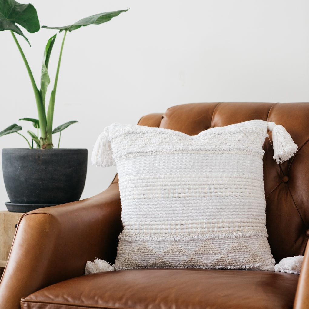 white textured pillow with corner tassels
