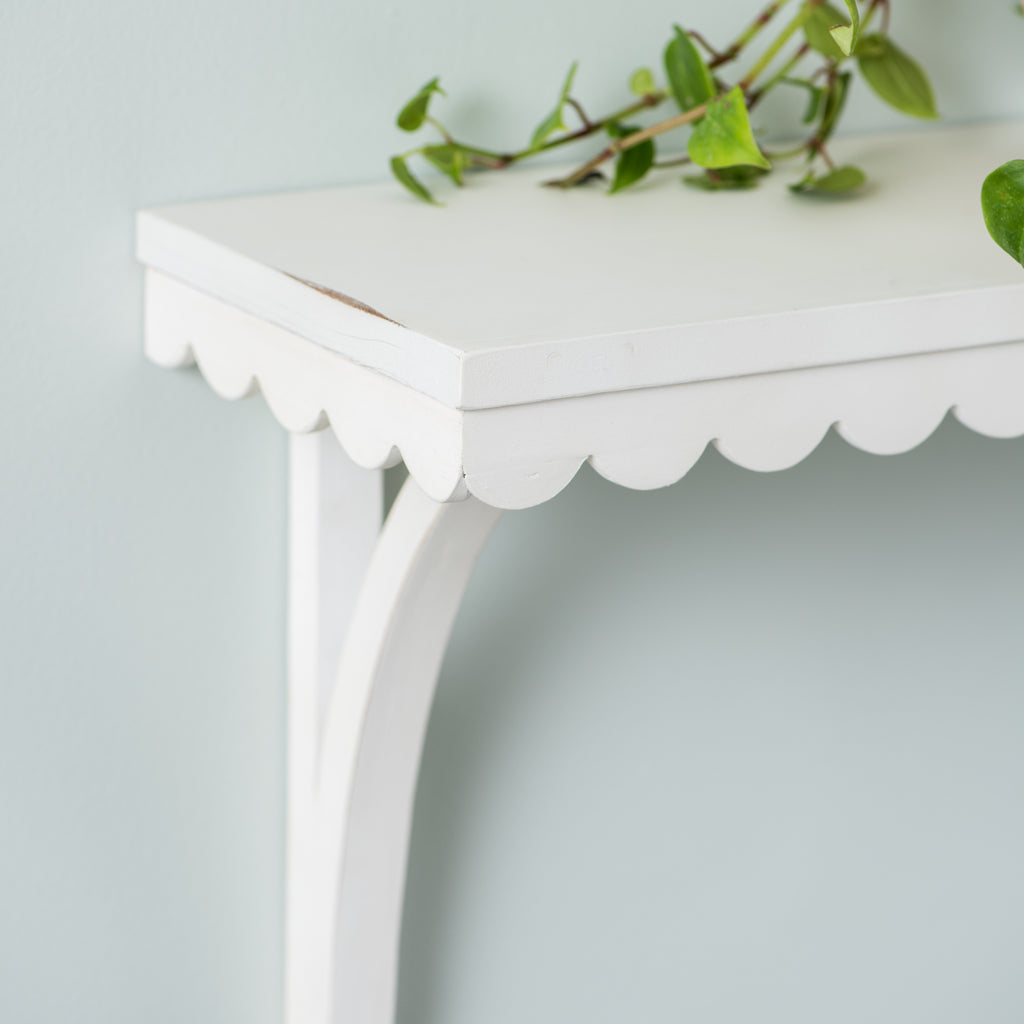 white wooden wall shelf with scalloped edge