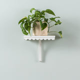 small white wooden wall shelf with scalloped edge