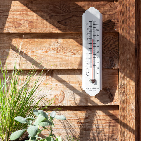 white metal outdoor wall thermometer