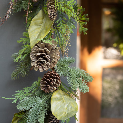 faux greenery garland featuring conifers, magnolia leaves, and pine cones