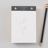 white desktop notepad with black binding