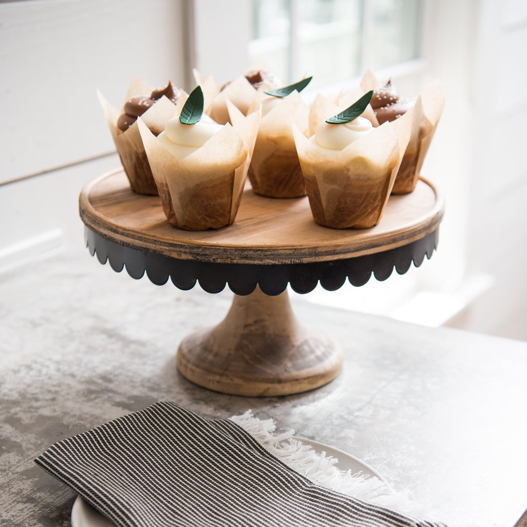 wood cake stand with a scalloped metal edge