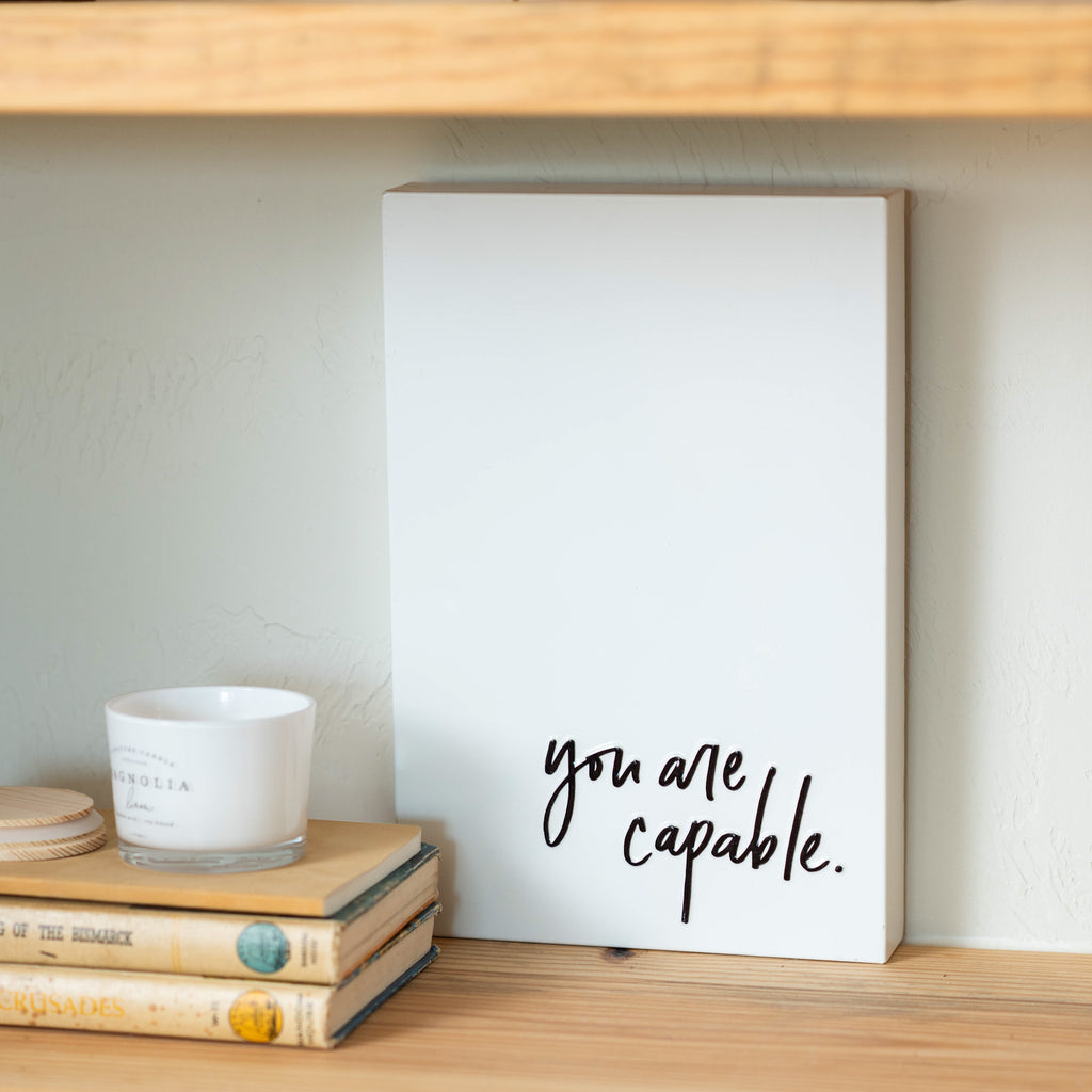 "white metal box sign with quote in black reading ""you are capable"" in script"