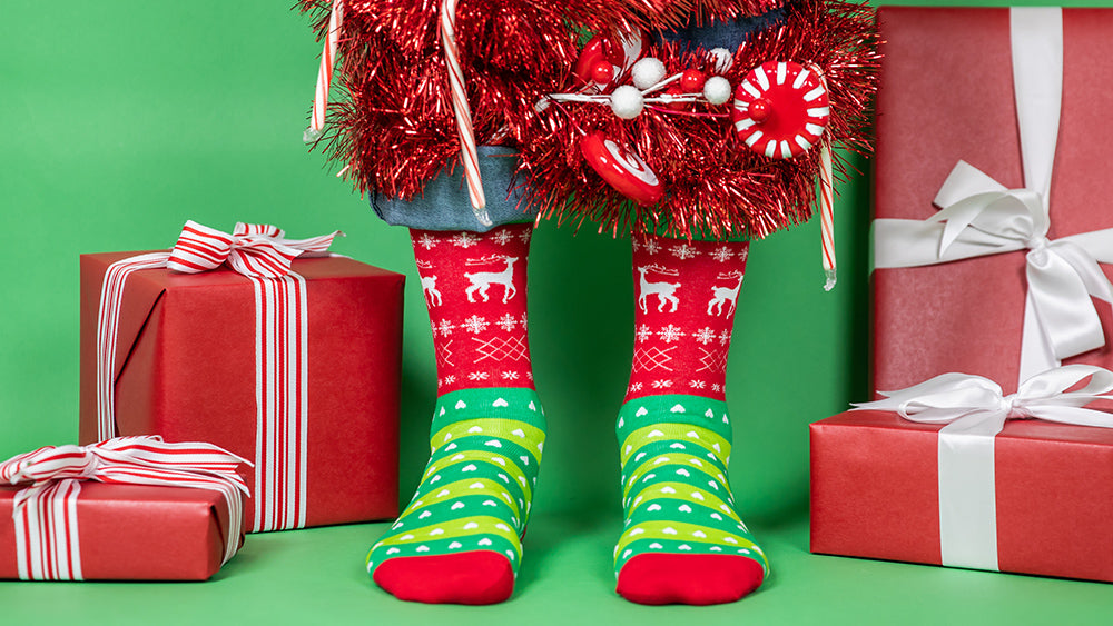 Model wearing Tacky Christmas Sweater socks and standing in front of presents