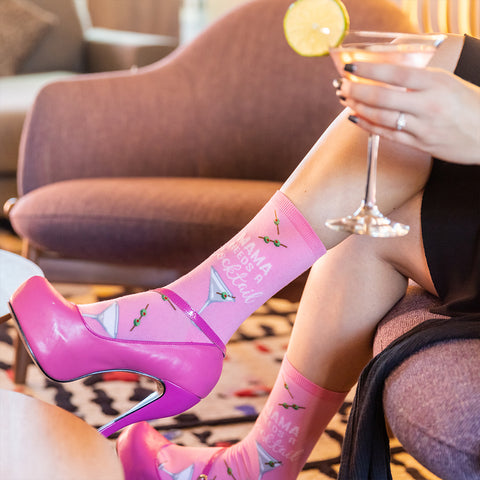 """woman wearing hot pink heels and socks that say, """"mama needs a cocktail"""""""