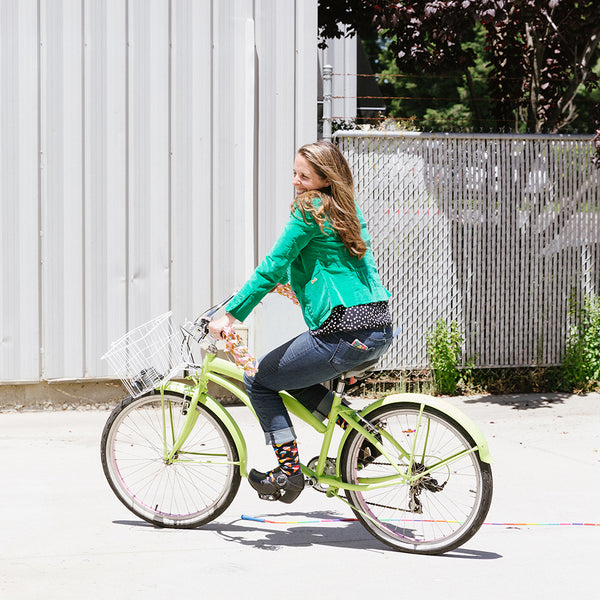 Brooke English riding a bicycle outside The Sock Drawer warehouse