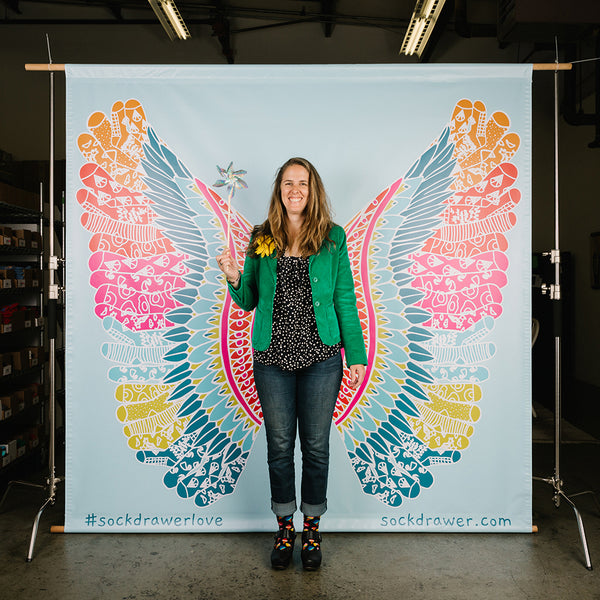 Brooke English posing in front of a mural with sock fairy wings