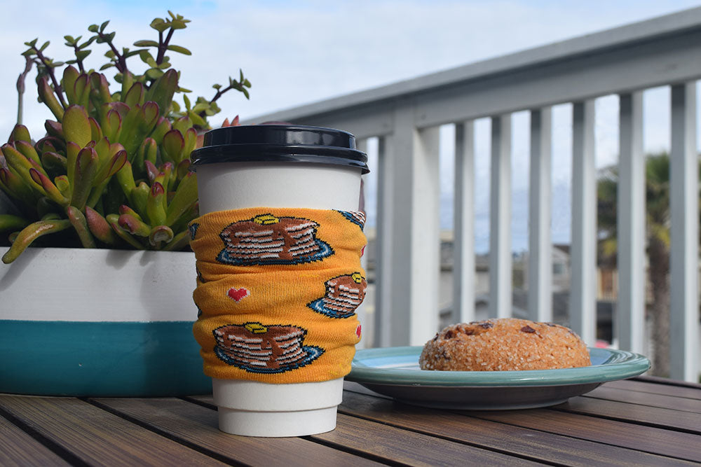 A coffee cup with a sleeve made from a pancake novelty sock