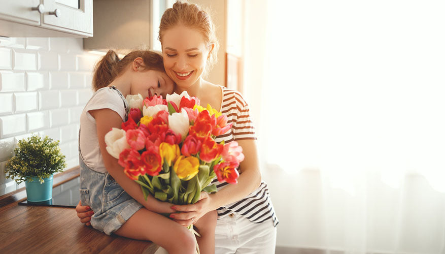 daughter giving mother flowers