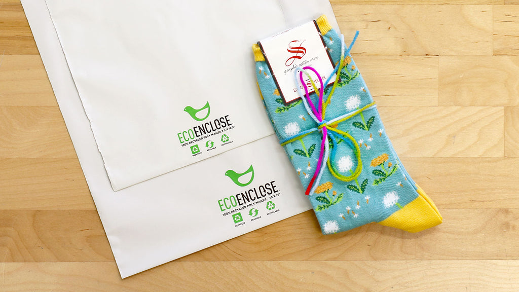 Our eco-friendly shipping bags next to a pair of fun novelty socks