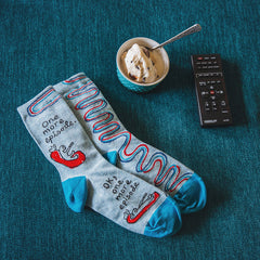 "Funny TV socks lying on a couch that say, ""One more episode"""