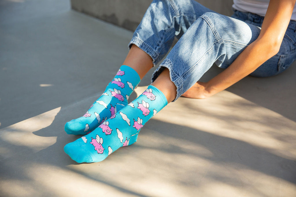 A woman wearing funny socks with flying pigs on them