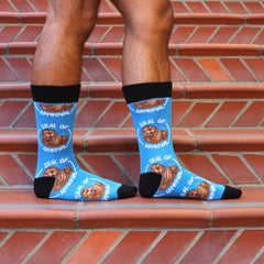 "A man wearing funny ""seal of approval"" socks with a seal giving a thumbs-up"