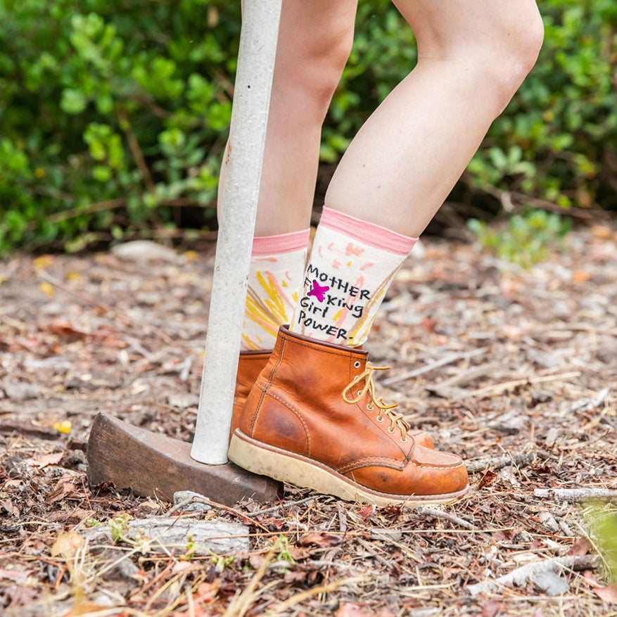 a woman modeling a pair of girl power socks in boots with an axe