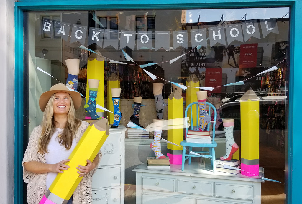 Graphic designer Jessica in front of The Sock Drawer shop window display