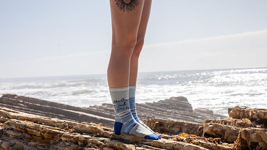 a woman wearing a pair of womens the ocean gets me socks at the beach