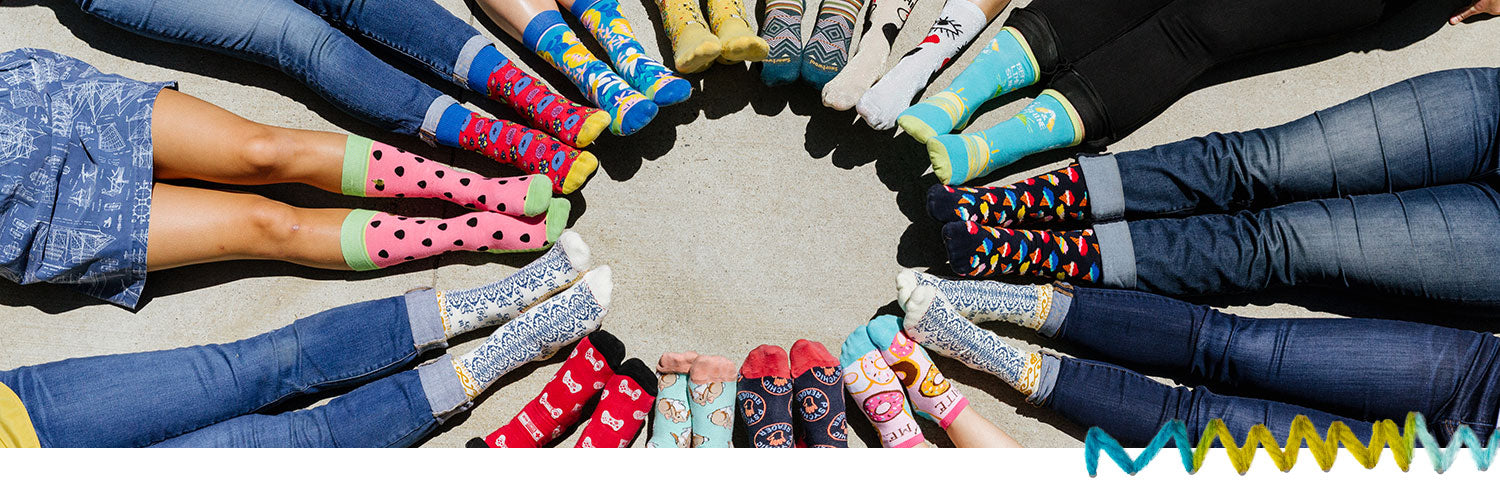 People sitting in a circle wearing fun novelty socks