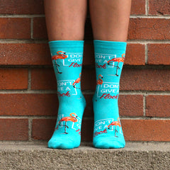 "A woman wearing funny flamingo socks that say, ""I don't give a flock"""