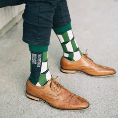 "A man wearing funny socks that say, ""This meeting is bullshit"""