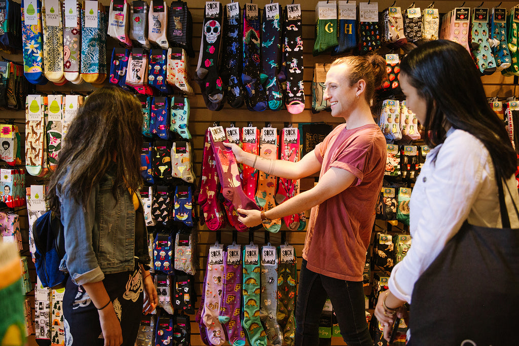 A Sock Drawer employee helps customers pick out styles in our shop