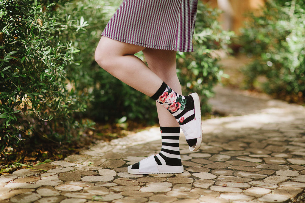A woman wearing striped rose socks with white sandals