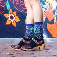A woman wearing Starry Night art socks with brown leather sandals