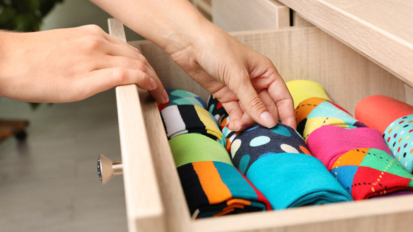 woman opening drawer with different colorful socks