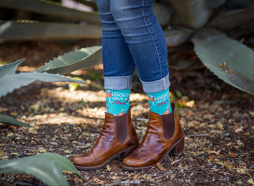 a woman showing off a pair of womens kbell dont give flock crew socks in boots