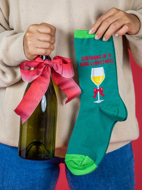 "woman holding a wine bottle and a pair of socks that say ""dreaming of a wine Christmas"""