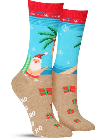 Funny non-skid Christmas socks for women, where Santa is shirtless on the beach with a surfboard