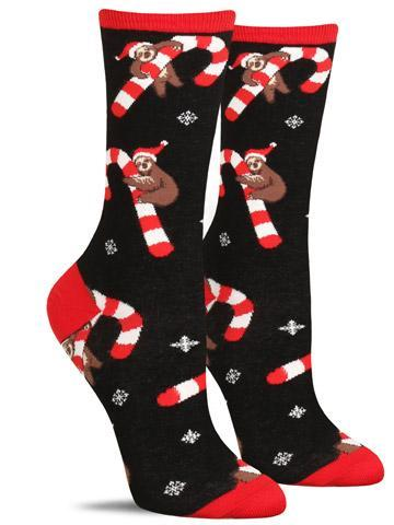 Funny Christmas socks for women in black with sloths in Santa hats hanging from candy canes