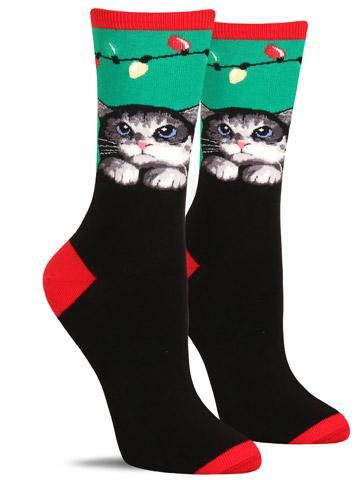 Cute Christmas socks with a mischievous cat looking at Christmas tree lights