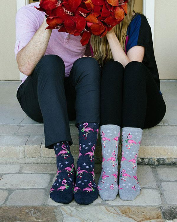 A man and a woman wearing matching funny tropical holiday socks with flamingos dressed in Santa hats