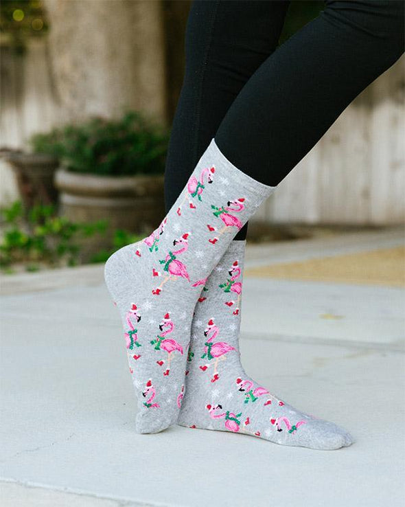 A woman wearing funny tropical holiday socks with flamingos dressed in Santa hats