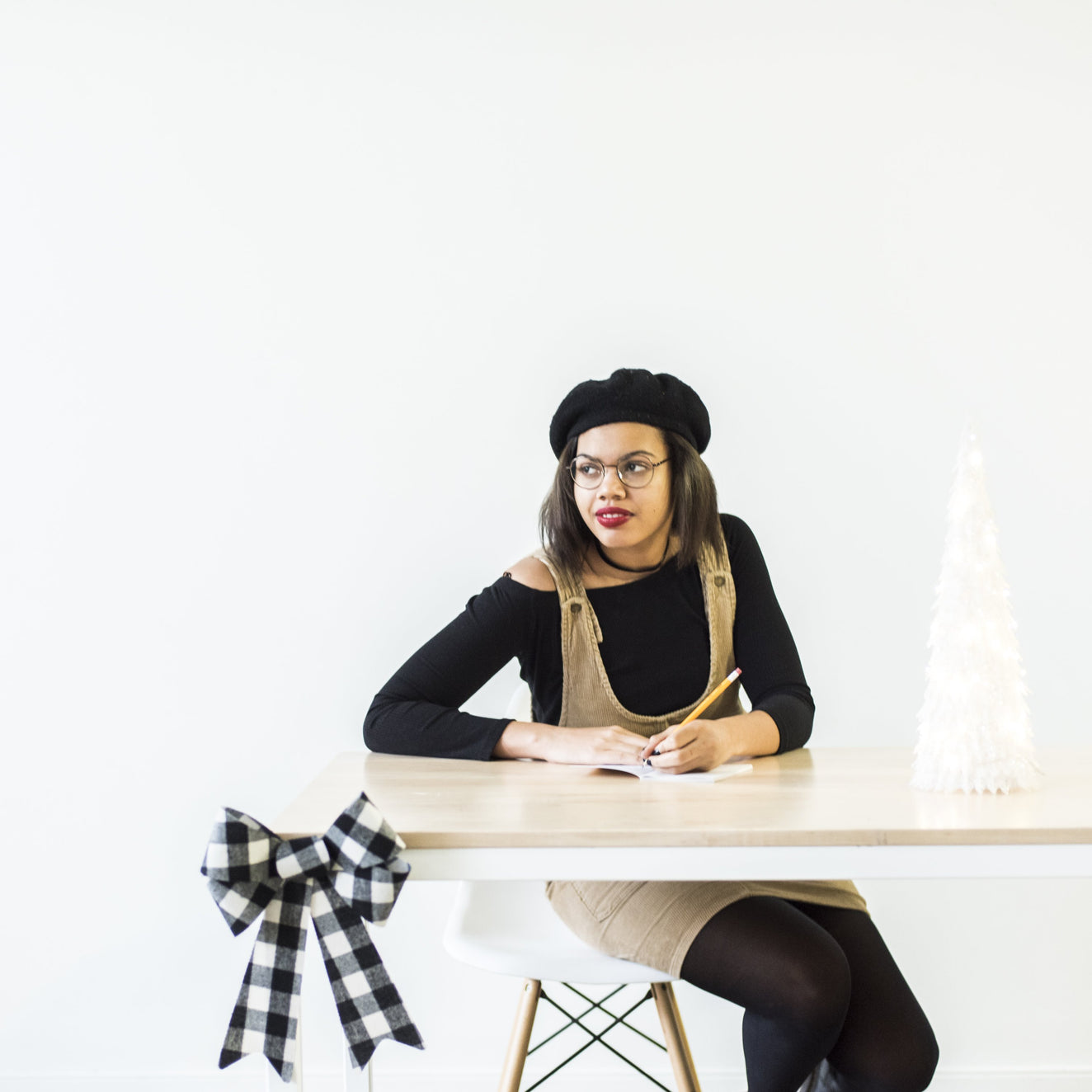 person at desk with bow and lit tree, wearing beret and red lipstick looking off while writing