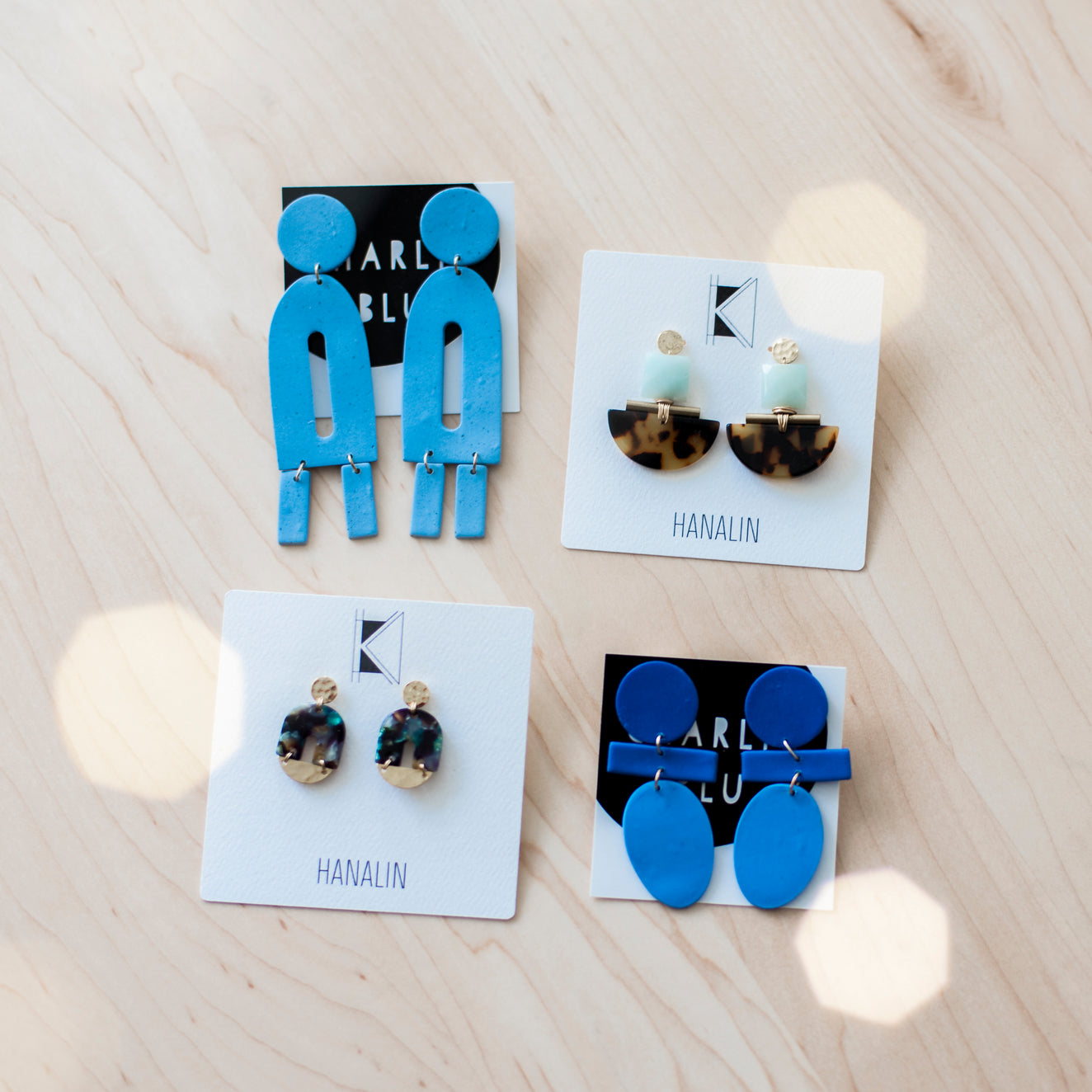 Earrings on a wood surface with twinkle lights