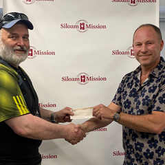 Jeff Appelt handing over a cheque to Siloam Mission in Winnipeg Manitoba.