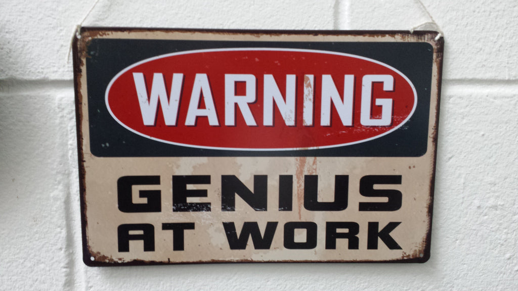 Metal 'Genius at Work' Signs